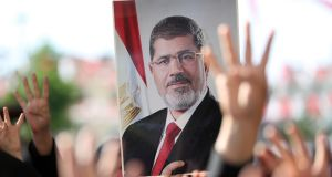 People hold a photograph of former  Egyptian president Mohamed Morsi during prayers for him in Istanbul, Turkey, on Tuesday, while his funeral was taking place in Egypt. Photograph: Erdem Sahin/EPA