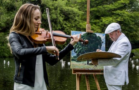 TUNING UP: Violinist Aoife Ní Bhriain and painter Blaise Smith performing in St Stephen's Green as part of the launch of the Secret Garden performances which have become part of the Kikenny Arts Festival which will open in August. Photograph: James Forde