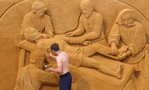 THE JUDGEMENT OF CAMBYSES: A sand carver works on a sculpture inspired by a painting by Gerard David during the Sand Sculpture Festival in Ostend, Belgium. Photograph: Yves Herman/Reuters