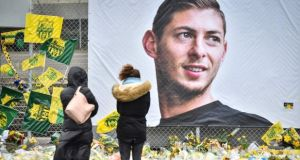 People look at yellow flowers displayed in front of the portrait of Argentinian forward Emiliano Sala at the Beaujoire stadium in Nantes, in February. Photograph: Loic Venance/AFP/Getty Images