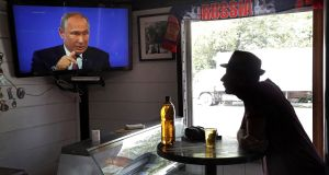 Man in bar watches Russian president Vladimir Putin on TV as he  answers citizens' questions during a live broadcast call-in conference. Photograph: Maxim Shipenkov