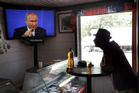 PUTIN POSITION: A man in a bar watches Russian president Vladimir Putin answer citizens' questions during a live call-in conference, in Podolsk. Photograph: Maxim Shipenkov/EPA