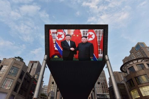 SHOW OF DIPLOMACY: Footage of Chinese president Xi Jinping in Pyongyang with North Korean leader Kim Jong-un is screened outside a mall in Beijing. Photograph: Greg Baker/AFP/Getty Images