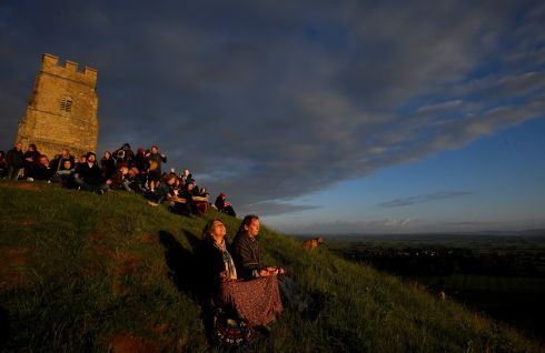 Revellers celebrate the summer solstice as the sun rises at Glastonbury Tor in Glastonbury, Somerset, England. Photograph: Toby Melville/Reuters