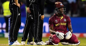 Carlos Brathwaite of West Indies is consoled by New Zealand players after he was  caught on the boundary to end the World Cup game at Old Trafford. Photograph:  Clive Mason/Getty Images