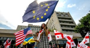 Protesters wave  EU, Georgian  and US flags during a protest  in Tbilisi against its government and Kremlin influence in the Black Sea state. Photograph: Getty Images