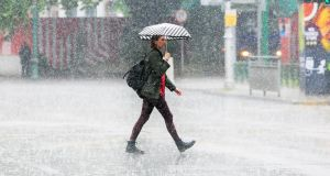 MONSOON SEASON? A woman crosses Northhumberland Road in Dublin during particularly heavy rain. Photograph: Gareth Chaney/Collins