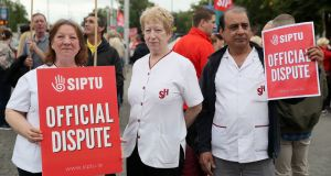 Health support workers Mag Dowling (L) Margaret Doherty (C) and Naveen Sharma (R), on strike outside St James's Hospital in Dublin on Wednesday. Photograph: Brian Lawless/PA