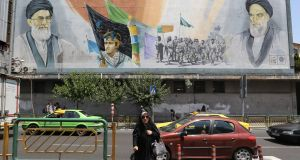 A woman in Tehran walks away from a mural of  Iran's supreme leader Ayatollah Ali Khamenei and the late founder of the Islamic Revolution, Ayatollah Ruhollah Khomeini: US sanctions take a deep toll. Photograph: Atta Kenare/AFP/Getty