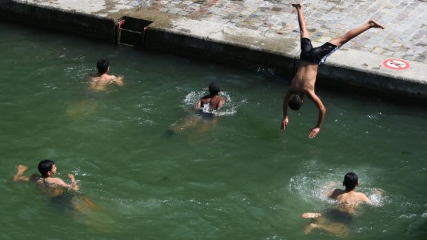 Diving into the waters of the Canal Saint-Martin in Paris. Photograph: Dominique Faget / AFP