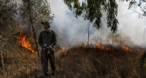 An Israeli soldier battles a fire started by an incendiary device launched from Gaza Strip, near the Israel and Gaza border fence on Wednesday. Photograph: AP Photo