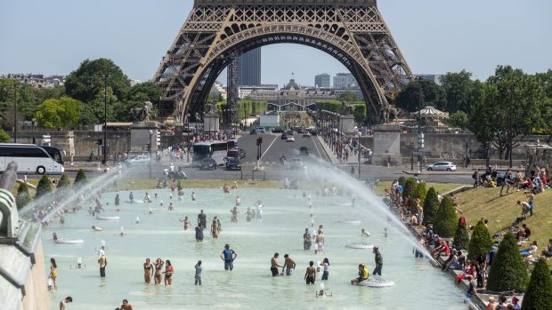 Parisians and tourists cool off in the Trocadero esplanade fountain near the Eiffel Tower in Paris, where the temperature rose to 37 degrees on Saturday. Photograph: Martin Barzilai/Bloomberg.