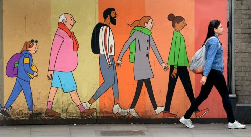 TAKE A WALK: Stepping into line with mural pedestrians on hoarding set up at Custom House Quay, Dublin. Photograph: Dara Mac Donaill
