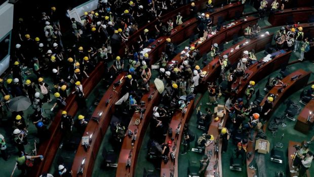 Protesters in Hong Kong took over the legislature's main building on Monday, tearing down portraits of legislative leaders and spray painting pro-democracy slogans on the walls of the main chamber. Photograph: Kin Cheung/AP