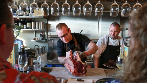 Rick Higgins (left) gets to work on a rib of beef