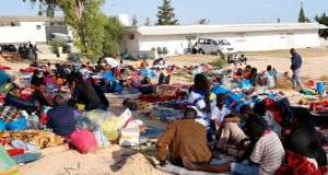 Migrants sit outside the  detention centre in the Tajoura suburb of Tripoli, Libya, which was  hit by an air strike earlier this week.   Photograph: Reuters/Ismail Zitouny