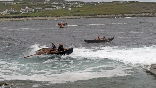 Currachs race through the waves at the Dooagh Day festival in Achill.