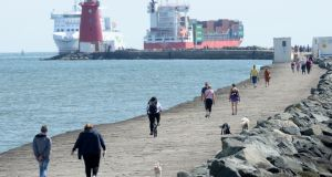 Busy port traffic as walkers enjoy the sunshine on the South Wall. Photograph: Alan Betson