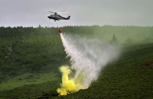 WILDFIRE READINESS: An Aer Corps AW 139 holicopter drops 1,200 litres of water on a simulated gorse fire during a Joint Wildfire Fire-Fighting Exercise between the Irish Air Corps and Wicklow Fire Service at Lough Dan, Co Wicklow. Photograph: Colin Keegan/Collins Dublin