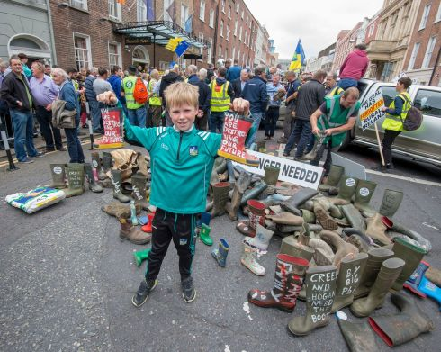Charlie Hanley, 9, from Co. Limerick holds slogan-daubed wellies outside the Dail today, which were brought in numbers by farmers who held a protest outside Dail Eireann today regarding the Mercosur trade deal between the EU and South American countries.  Photograph: Dave Meehan for the Irish Times