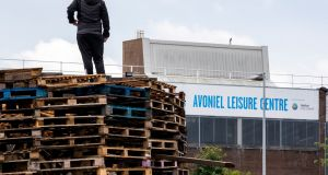 A bonfire builder on the contentious  bonfire at Avoniel Leisure Centre in Belfast. Photo credit should read: Liam McBurney/PA Wire