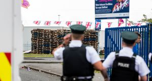 PSNI officers standing outside the entrance to Avoniel Leisure Centre, where an 11th night bonfire has been erected. Photograph: Liam McBurney/PA Wire