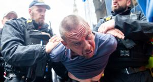 A men  is detained by police after scuffles broke out   following the sentencing of Tommy Robinson in London. Photograph:  Luke Dray/Getty Images