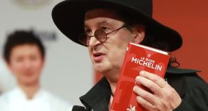 Marc Veyrat holding a Michelin guide in 2018, when La Maison des Bois was awarded the maximum three stars. Photograph: Jacques Demarthon/Getty Images