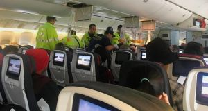 Emergency staff   treat a passenger on the Air Canada flight to Australia that was diverted and landed in Honolulu. Photograph: Hurricane Fall via AP