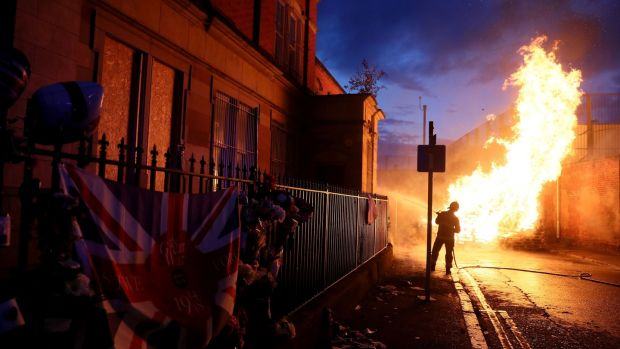 Members of the fire service work to contain the bonfire on Cluan Place, Belfast on Thursday night. Photograph: Brian Lawless/PA