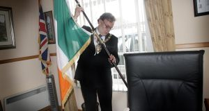 Belfast's former lord mayor Tom Hartley places a tricolour beside the union jack in his mayoral office in Belfast city centre