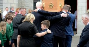 Sinead McSweeney and her son Séamus follow the remains of  husband and father Noel Whelan at the Church of the Holy Name in Ranelagh. Photograph: Alan Betson/The Irish Times