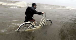 Tyler Holland guides his bike through the water as winds from Tropical Storm Barry push water from Lake Pontchartrain over the seawall. Photograph: David J Phillip/AP Photo