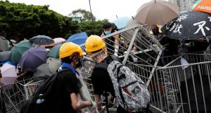 Anti-extradition bill protesters set up barriers, held together with cable ties, as they face riot police after a march in Hong Kong.Photograph:Tyrone Siu/Reuters