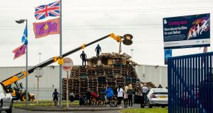 Crowd gathers to watch men remove material from a July 11th night bonfire.  Photograph:  PA Wire