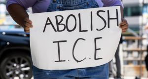 A protester holds a sign reading 'Abolish ICE' in front of the Metropolitan Detention Center in downtown Los Angeles, California. Photograph: Etienne Laurent/EPA