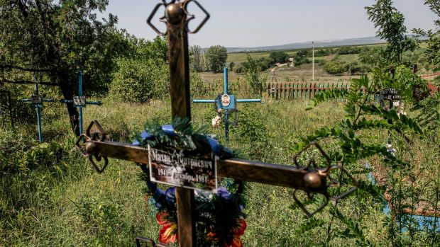 The graveyard in Dobrusa, Moldova is slowly receding into an undergrowth of nettles and bramble, grass flowers and cow parsley. Photograph: Laetitia Vancon/The New York Times