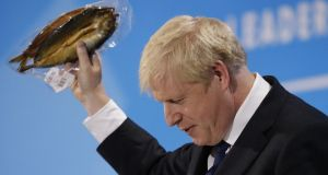 Conservative MP and leadership contender Boris Johnson holds up kipper fish in plastic packaging as he speaks at the final Conservative Party leadership election hustings in London. - Photograph: Tolga Akmen/AFP/Getty Images