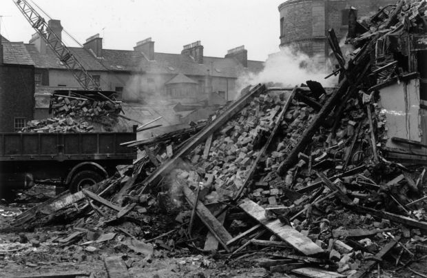 Trucks clear away the debris of a bombed building in Belfast, September 1969. Photograph: Evening Standard/Getty