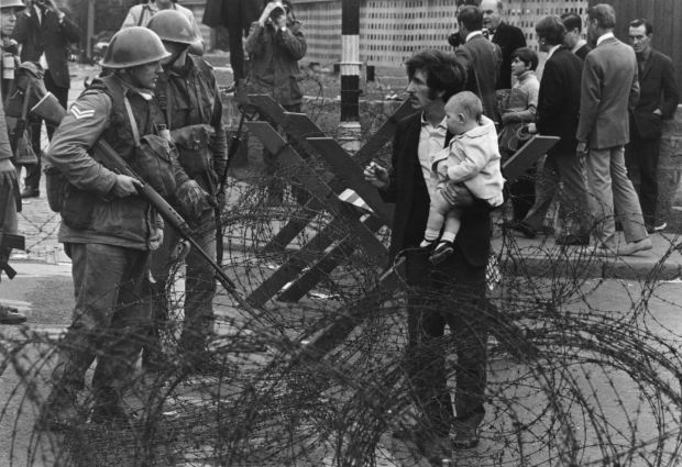 British soldiers stop a man trying to carry his baby through a barbed-wire barricade on the Falls Road area of Belfast. Photograph: James Jackson/Getty
