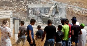 Palestinians watch  Israeli security forces tear down a building still under construction in the Wadi al-Hummus area close to the Palestinian village of Sur Baher. Photograph:   Hazem Bader/AFP