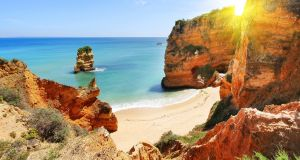 A picturesque beach at sunset in Lagos, Portugal. Photograph: Sergei Aleshin/Getty