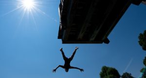 A boy jumps from a diving platform into the lake Ammersee in Utting, southern Germany. Photograph:  Sven Hoppe/dpa/AFP