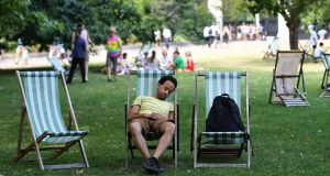 A man falls asleep during the heat at St James Park in London on Thursday. Photograph: Andy Rain/ EPA