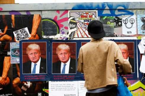 A person photographs an artwork entitled 'DORIS BORUMP' by artist STOT21stcplanB that depicts both US president Donald Trump and British prime minister Boris Johnson on a wall in east London, Britain. Photograph: Henry Nicholls/Reuters