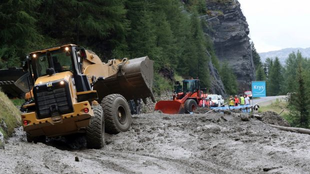 Workers use diggers to clear the road at the 19th stage of the Tour de France on Friday. Photograph: Thibault Camus/AP