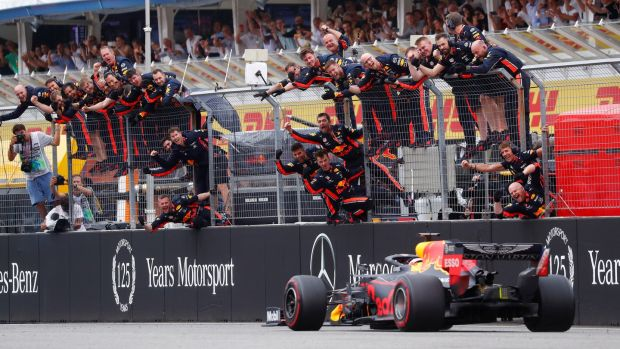 Max Verstappen crosses the line to win the race as Red Bull engineers celebrate. Photograph: Kai Pfaffenbach/Reuters