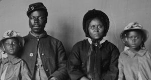 African American soldier in uniform, with his wife  and two daughters. Photograph: Buyenlarge/Getty Images