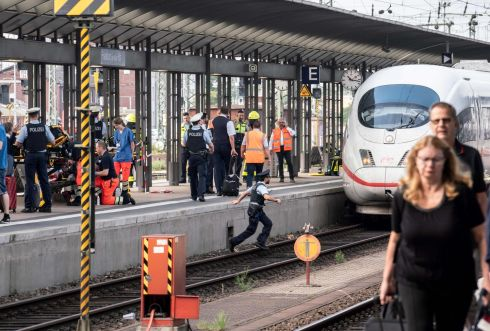 PUSHED: Police and medical helpers stand next to an ICE high speed train at Frankfurt's main station after a man pushed a child in front of the moving train. The eight-year-old boy died after he was pushed along with his mother in front of the train by a 40-year-old man, police said. The suspect, who was allegedly unrelated to the victims, ran off but was overpowered by passers-by and detained by police. The woman was being treated in hospital after narrowly escaping from the tracks where an arriving ICE speed train ran over her child. Photograph: Frank Rumpenhorst/dpa/AFP/Germany/Getty Images