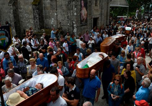 "PROCESSION: People are carried in coffins by relatives during the annual ""Procession of the Shrouds"" to celebrate Saint Martha ""the Saint of resurrection"" in the village of Santa Marta de Ribarteme, northwestern Spain, near Nieves. People who have escaped death lie in caskets and are carried in procession by relatives in a thankful gesture for being kept alive. Photograph: Miguel Riopa/AFP/Getty Images"